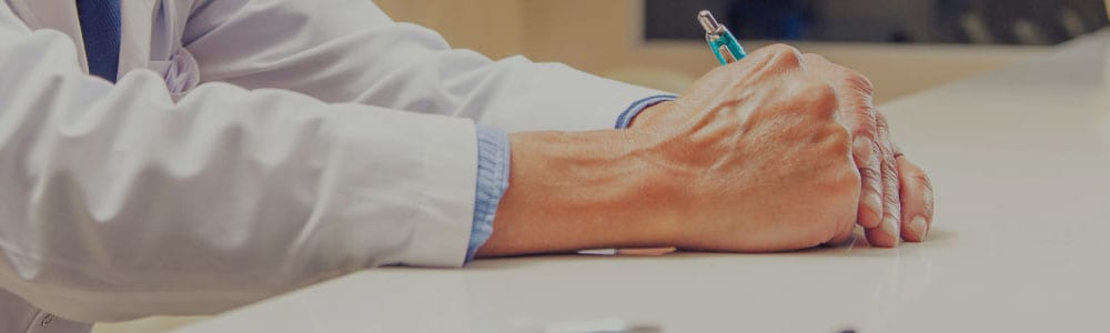 Doctor writing at his desk