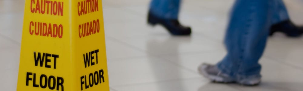 People walking by a wet floor sign